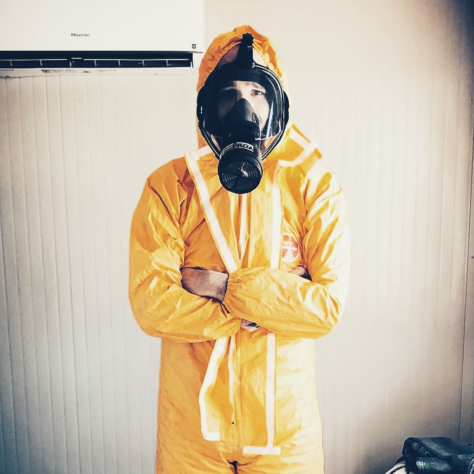 Person in Hazardous Materials coverall - symbolizing safety.